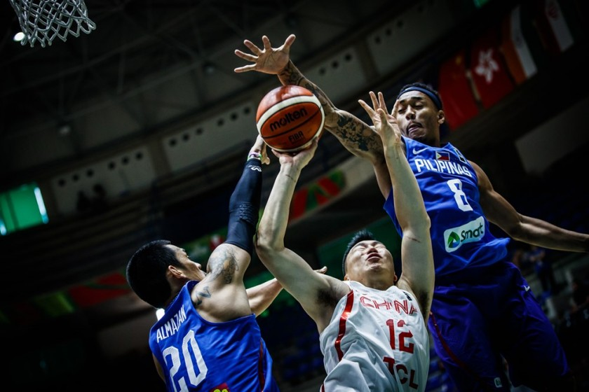 Raymond Almazan (L) and Calvin Abueva (R) of the Philippines smother Gen Li of China | FIBA photo