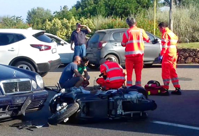 "Ambulance personnel tend to a man lying on the ground, later identified as actor George Clooney, after being involved in a scooter accident in the near Olbia, on the Sardinia island, Italy, Tuesday, July 10, 2018. Actor George Clooney was taken to the hospital in Sardinia on Tuesday and released after being involved in an accident while riding his motor scooter, hospital officials said. ""He is recovering at his home and will be fine,"" spokesman Stan Rosenfield told The Associated Press in an email. The John Paul II hospital in Olbia confirmed Clooney had been treated and released after Tuesday's accident. Local media that had gathered at the hospital said Clooney left in a van through a side exit. (AP Photo/Mario Chironi)"