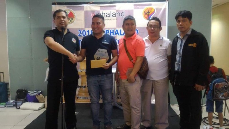 "National Master (NM) lawyer Bob Jones Liwagon of the Philippine Army (second from left) receive his top prize P10,000 plus elegant trophy to Philippine Executive Chess Association (PECA) founding president Atty. Cliburn Anthony A. Orbe (first from left) for winning the  sixth leg Alphaland National Executive Chess Championship was held last June 30, 2018 at the Activity Hall, Second Floor, Alphaland Makati Place in Malugay Street, Makati City .Also in photo were IT expert Joselito Cada, 7-times Philippine Executive Champion Dr. Jenny Mayor and Dr. Alfredo ""Fred"" Paez."