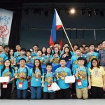 Filipino students together with their coaches wave the Philippine flag and show the medals and trophies they won at the awarding ceremony of the 2018 Bulgaria International Mathematics Competition (BIMC) in Burgas, Bulgaria. (Photo by MTG via PIA.gov.ph)