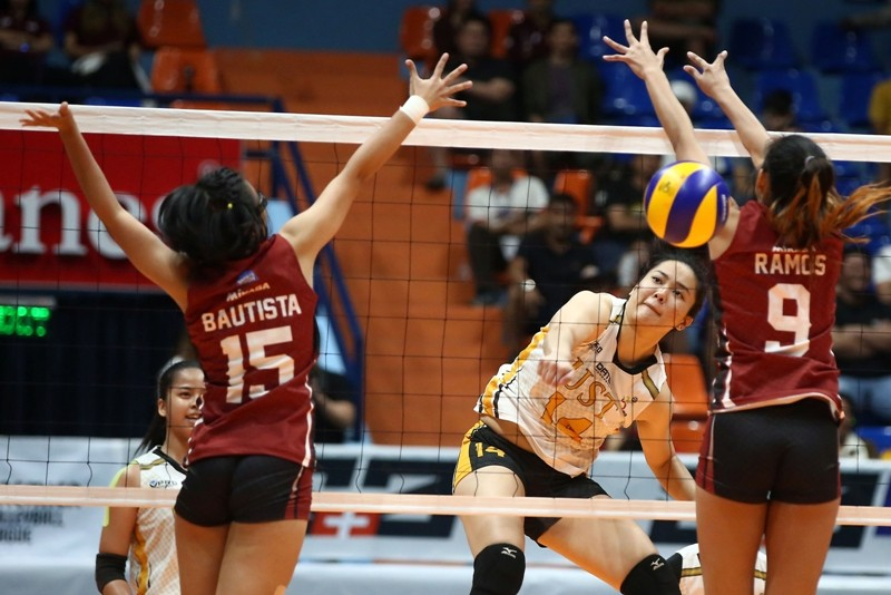 Christine Francisco of UST hammers in a power hit against UP's Jessma Ramos and Mary Bautista during their PVL Collegiate Conference clash at the Filoil Arena.