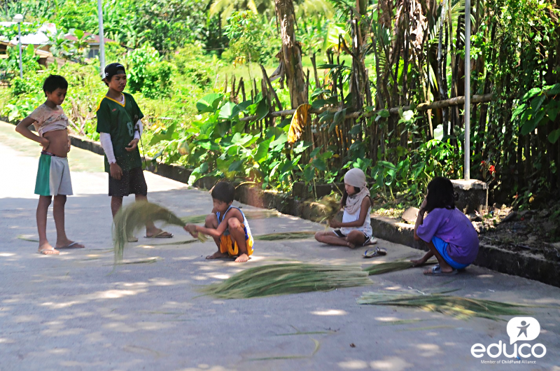Children making Filipino brooms (walis ting-ting) made out of grass in Catanduanes.