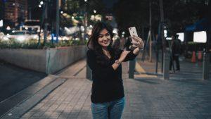 woman taking selfie, mobile app [Photo by Afif Kusuma on Unsplash]