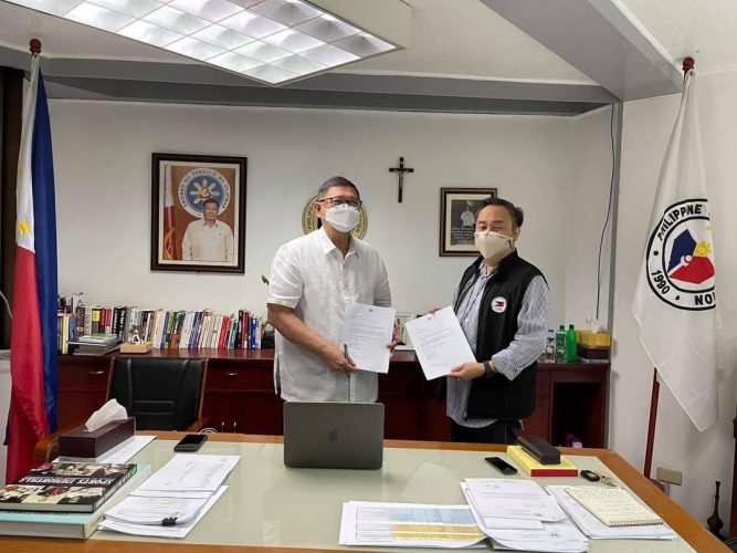 """PHILIPPINE Olympic Committee President Rep. Abraham """"Bambol"""" Tolentino (right) turns over to Philippine Sports Commission (PSC) Chairman William Ramirez the country's entry by numbers for the Vietnam 31st Southeast Asian Games."""