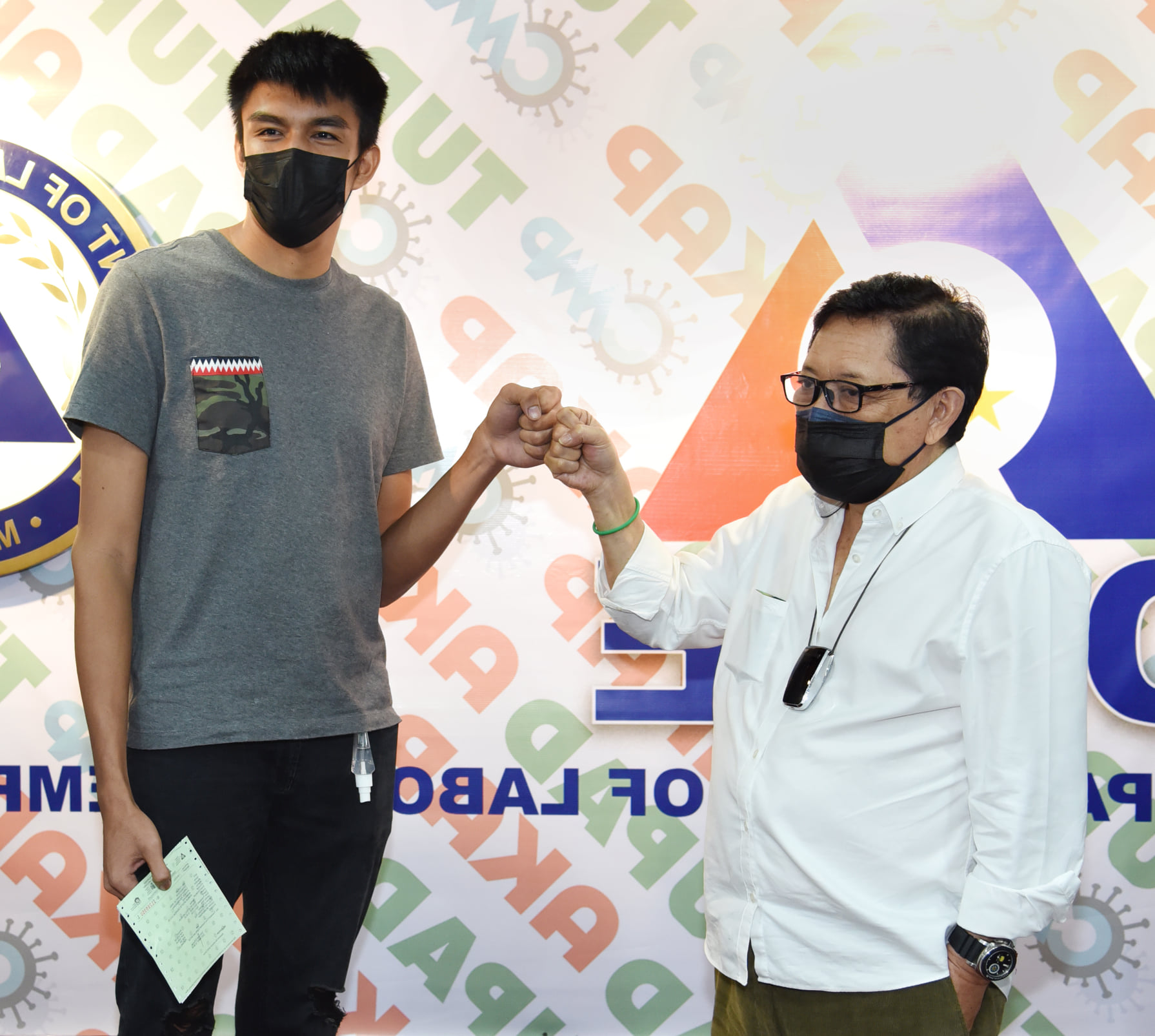 Department of Labor and Employment Secretary Silvestre 'Bebot' Bello III awards the overseas employment certificate (OEC) to Gilas Pilipinas forward Kemark Carino (right).  [photo from DOLE Facebook]